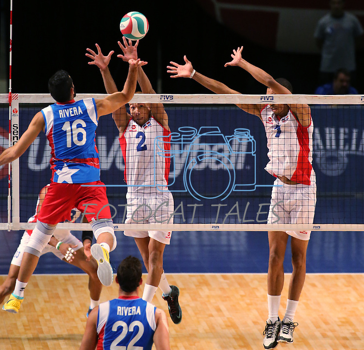 Jackson Rivera with Puerto Rico hits at Dominican Republic blockers Cabulla Alcantara and Tavares Frias during the Pan American Cup at the Reno Events Center in Reno, Nev., on Monday, Aug. 17, 2015. <br /> Photo by Cathleen Allison