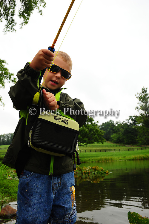 In the summer a young boy fishing in a pond with a raincoat on in northeast PA