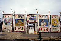 Coney Island, New York - Side Show posters advertise a two headed baby line the street in Coney Island.