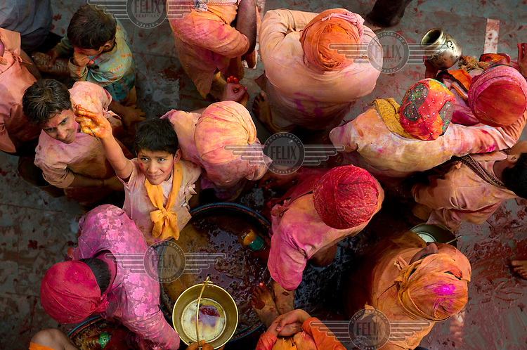 Coloured powders are released over devotees gathered at the Krishna Temple of Shriji, during Lathmar Holi.