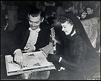 BNPS.co.uk (01202 558833)<br /> Pic:  Juliens/BNPS<br /> <br /> Clark Gable and Vivien Leigh playing a board game between filming scenes.<br /> <br /> Amazing behind the scenes photos of the classic film Gone With The Wind have come to light 80 years later.<br /> <br /> The comprehensive archive of over 800 images includes candid snaps of the leads Clark Gable and Vivien Leigh unwinding between takes.<br /> <br /> One extraordinary photo shows the pair still in costume playing a board game, with another capturing the burning of Atlanta in the film.<br /> <br /> There is also a picture of the director Victor Fleming holding the novel 'Gone With The Wind' while in discussion with Leigh.