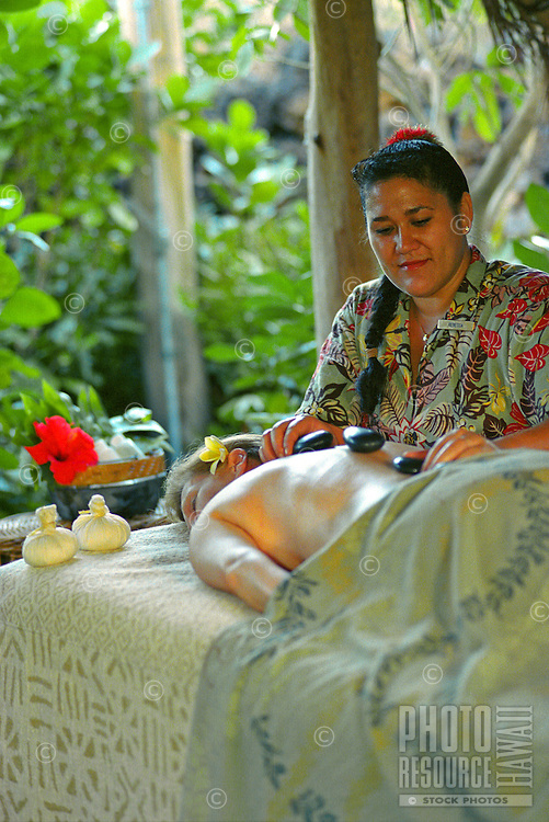 Woman recieving Pohaku, hot stone therapy, at the Mauna Lani spa on the Big Island of Hawaii