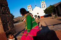 "A Cora Indian woman sits in front of the church before the religious ritual ceremony of Semana Santa (Holy Week) in Jesús María, Nayarit, Mexico, 20 April 2011. The annual week-long Easter festivity (called ""La Judea""), performed in the rugged mountain country of Sierra del Nayar, merges indigenous tradition (agricultural cycle and the regeneration of life worshipping) and animistic beliefs with the Christian dogma. Each year in the spring, the Cora villages are taken over by hundreds of wildly running men. Painted all over their semi-naked bodies, fighting ritual battles with wooden swords and dancing crazily, they perform demons (the evil) that metaphorically chase Jesus Christ, kill him, but finally fail due to his resurrection. La Judea, the Holy Week sacred spectacle, represents the most truthful expression of the Coras' culture, religiosity and identity."