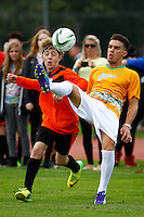 London, UK on Sunday 31st August, 2014. Bailey McConnell (left)  almost gets his head kick by a member of The Janoskians team during the Soccer Six charity celebrity football tournament at Mile End Stadium, London.