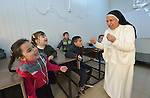 Sister Anahid, a member of the Dominican Sisters of St. Catherine of Siena, interacts with students in a primary school she supervises in Dohuk, Iraq. Most of the students were displaced from their home villages when the Islamic State group took over portions of the Nineveh Plains in 2014. Because they came from communities with Arabic curriculum schools, they often don't fit well in schools in the villages where they resettled, because those schools teach in Kurdish or Assyrian. So the religious order started the school, which has students from several faiths, including Islam and Christianity. The Christian Aid Program Nohadra - Iraq (CAPNI) provides transportation for many students to Dohuk from the rural villages where their families have taken refuge.