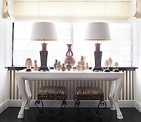 Two lamps and a collection of urns and statuettes stand on a white table. Underneath are a pair of 1940s French stools are upholstered in a Brunschwig & Fils linen. The table stands in a bay window dressed with a Roman blind in cream.