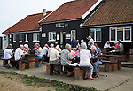 Elderly people eating outside eating fish and chips at the Flora tea rooms cafe, Dunwich, Suffolk, England,