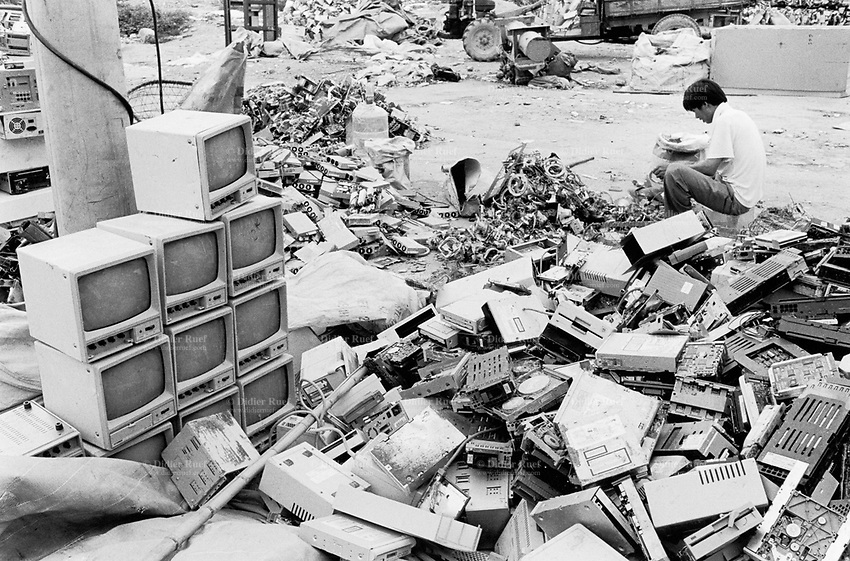 China. Province of Guangdong. The village of Nanyang is part of the town of Guiyu. Workers take down by hand old computers, dicarded monitors and electronic components which lay on the ground. The various parts will be recycled for its metals, electric cables, terminals, printed and integrated circuits, chips,... © 2004 Didier Ruef