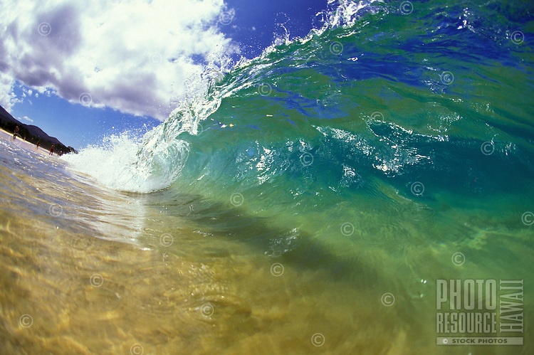 Small blue wave crashing on shoreline of Makena beach, Maui