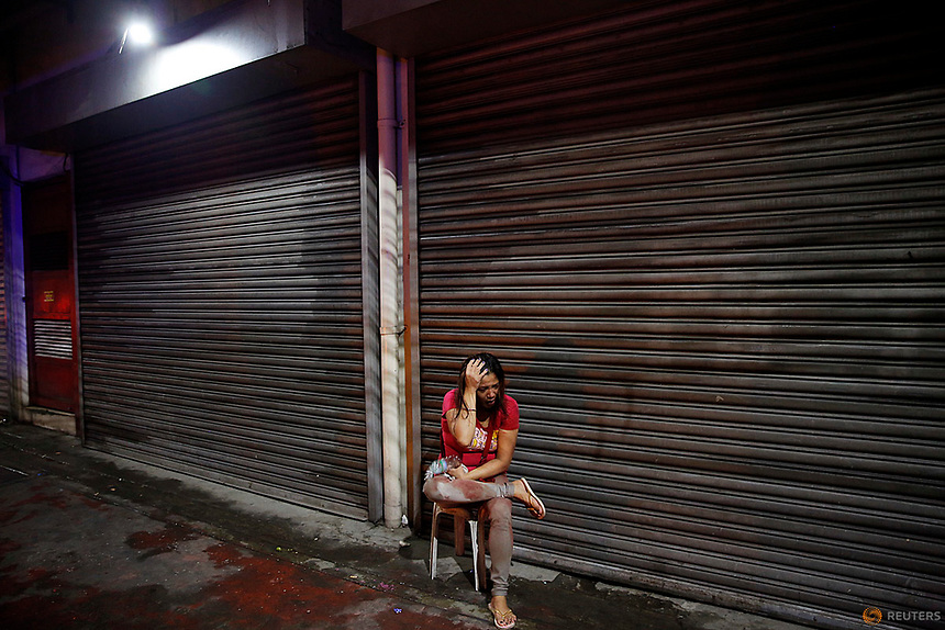 A woman covered in blood holds her head after her husband was shot dead by unidentified gunmen riding motorcycles in Manila, Philippines late October 10, 2016.  REUTERS/Damir Sagolj