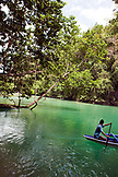 PHILIPPINES, Palawan, Sabang, a man paddles his canoe to the entrance of the Underground River