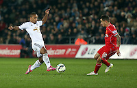 SWANSEA, WALES - MARCH 16: L-R Wayne Routledge of Swansea attempts to pass the ball past Philippe Coutinho of Liverpool during the Premier League match between Swansea City and Liverpool at the Liberty Stadium on March 16, 2015 in Swansea, Wales