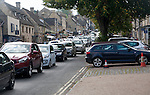 Tourist honeypot village street crowded with traffic in Burford, Oxfordshire, England, UK