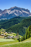 Italy, South Tyrol (Trentino - Alto Adige), La Valle: hamlet Tolpei with steeple of parish church St Genesius in Old-Wengen, at background Heiligkreuzkofel mountain (Sasso di Santa Croce) at Fanes-Sennes-Prags Nature Park | Italien, Suedtirol (Trentino - Alto Adige), Wengen: der Weiler Tolpei mit dem Turm der alten Pfarrkirche St. Genesius in Altwengen, im Hintergrund thront der Heiligkreuzkofel (Sasso di Santa Croce) im Naturpark Fanes-Sennes-Prags