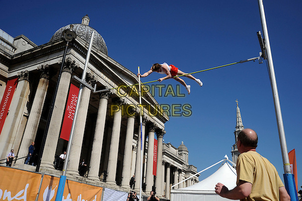 POLE VAULTER.Holland House 2010 event to celebrate Holland's national day, Trafalgar Square, London, England..April 17th, 2010.atmosphere gv general view sport athlete vaulting vault jump jumping gesture national gallery .CAP/IA.©Ian Allis/Capital Pictures.