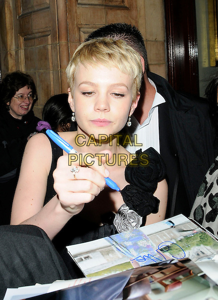 CAREY MULLIGAN.Outside  - The 30th London Critics' Circle Film Awards, Landmark Hotel, Landmark Hotel, London, England, UK, 18th February 2010..half length pen black corsages rosettes flowers signing autographs fans .CAP/CAN.©Can Nguyen/Capital Pictures