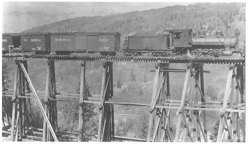 RGS 2-8-0 #19 on Bridge 43-A while B&amp;B supplies are lowered to the base for maintenance.<br /> RGS  Ames, CO  Taken by Virden, Walter - pre 1920