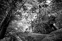 Switzerland. Canton Fribourg. The forest around Hauterive Abbey. Alain Devaud (R) stands on a rock. A teenager couple is seated and kissing on another rock. Hauterive Abbey (Abbaye d'Hauterive) is a Cistercian abbey in the Swiss municipality of Hauterive in the canton of Fribourg. It is a Swiss heritage site of national significance. The entire Hauterive area is part of the Inventory of Swiss Heritage Sites. 3.05.2020 © 2020 Didier Ruef