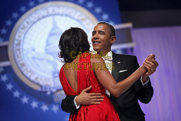 Michelle Obama & Barack Obama.2013 Inauguration Ball, Washinton D.C., USA..January 21st, 2013.half length black suit tuxedo red dress back behind rear holding hands married husband wife dance dancing arm around waist   .CAP/ADM/CNP/CS.©Chip Somodevilla/CNP/AdMedia/Capital Pictures