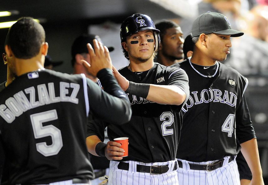 26 MAY 2010: Colorado Rockies shortstop Troy Tulowitzki celebrates a run in the dugout with teammates during a regular season Major League Baseball game between the Colorado Rockies and the Arizona Diamondbacks at Coors Field in Denver, Colorado. The Rockies beat the Diamondbacks 7-3. *****For Editorial Use Only*****