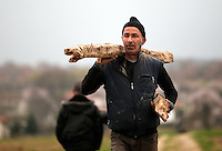 Pictured: A man carries wood to the camp Monday 29 February 2016<br /> Re: A crowd of migrants has burst through a barbed-wire fence on the FYRO Macedonia-Greece border using a steel pole as a battering ram.<br /> TV footage showed migrants pushing against the fence at Idomeni, ripping away barbed wire, as FYRO Macedonian police let off tear gas to force them away.<br /> A section of fence was smashed open with the battering ram. It is not clear how many migrants got through.<br /> Many of those trying to reach northern Europe are Syrian and Iraqi refugees.<br /> About 6,500 people are stuck on the Greek side of the border, as FYRO Macedonia is letting very few in. Many have been camping in squalid conditions for a week or more, with little food or medical help.