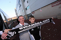 Pictured: Two Swansea supporters just about to get on one of the dozens of coaches used to transport them to London from the Liberty stadium, ahead of today's clash. Sunday 24 February 2013<br /> Re: Capital One Cup final, Swansea v Bradford at the Wembley Stadium in London.