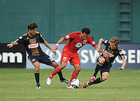 DC United midfielder Dwayne De Rosario (7) gets challenged by Philadelphia Union midfielder Brian Carrroll (7) right and midfielder Veljko Paunovic (16) left.  Philadelphia Union tied DC United 2-2, at RFK Stadium, Saturday July 2, 2011.