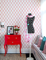 A bold red and white patterned wallpaper is complimented by cushions in geometric fabrics, while a Georgian style side table is updated with bright red paint.