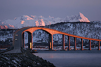 Cars pass over a bridge as the sun sets.  Lofoten is where the World's largest and last cod stocks are found, in the Barent's Sea. Fishing is as strong an industry as tourism in this region.
