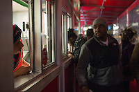 A Tasty Burger employee looks out from the outdoor pick-up window at Tasty Burger on Boylston Street in the Fenway neighborhood of Boston, Massachusetts, USA, in the early hours of Saturday, Dec. 5, 2015.