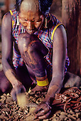 A-Ukre village, Xingu, Brazil. Kayapo woman with black body paint crushing Brazil nuts.