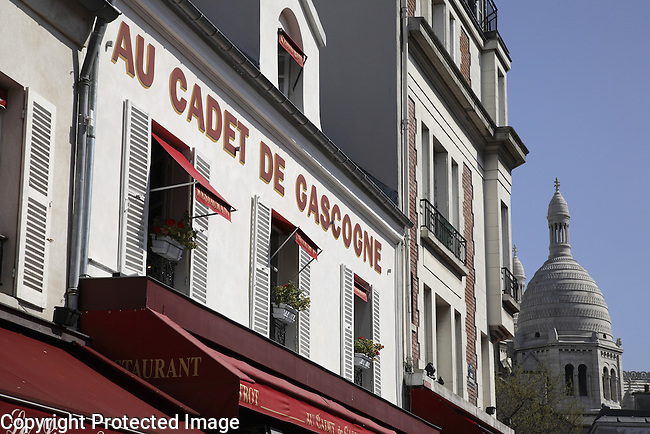 Facades in Montmartre with the Sacre Coueur in the background, Paris, France