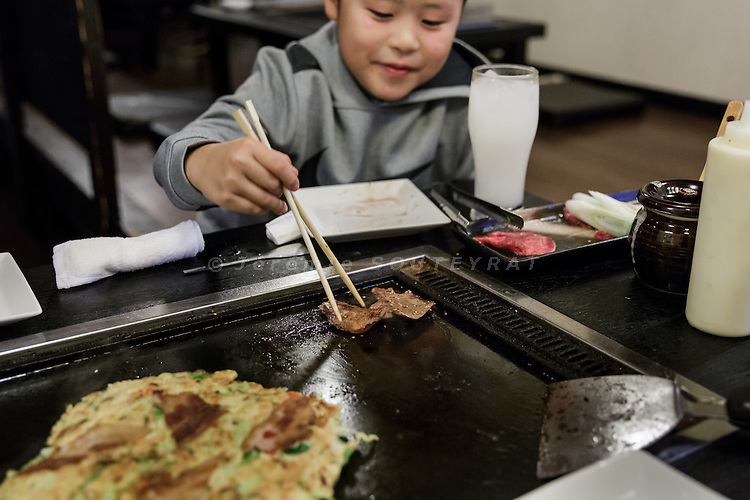 Tokyo, Japan, November 19 2016 - Souta OBI, a 8-year old sumo wrestler and his mother in a restaurant after the training, eating grilled beef and okonomiyaki (Japanese salty pancake containing a variety of ingredients).