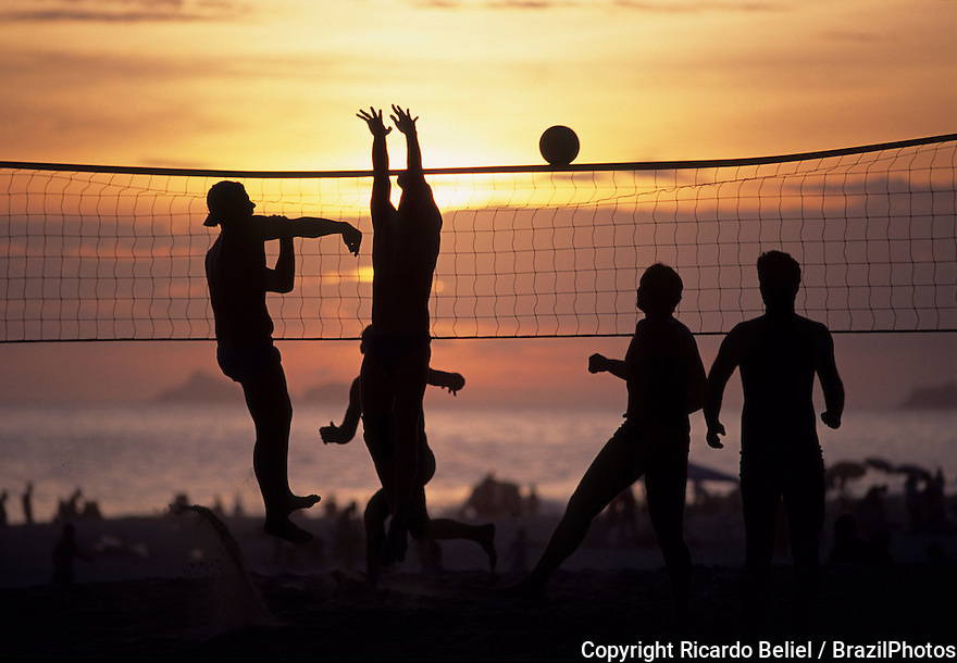 Beach volley-ball or beach volleyball at Ipanema beach sunset, Rio de Janeiro, Brazil - an attacking move characterized by a forward thrust of the player who hits the ball with the open hand.