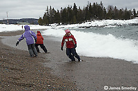 Young kids racing the lake waves in the winter