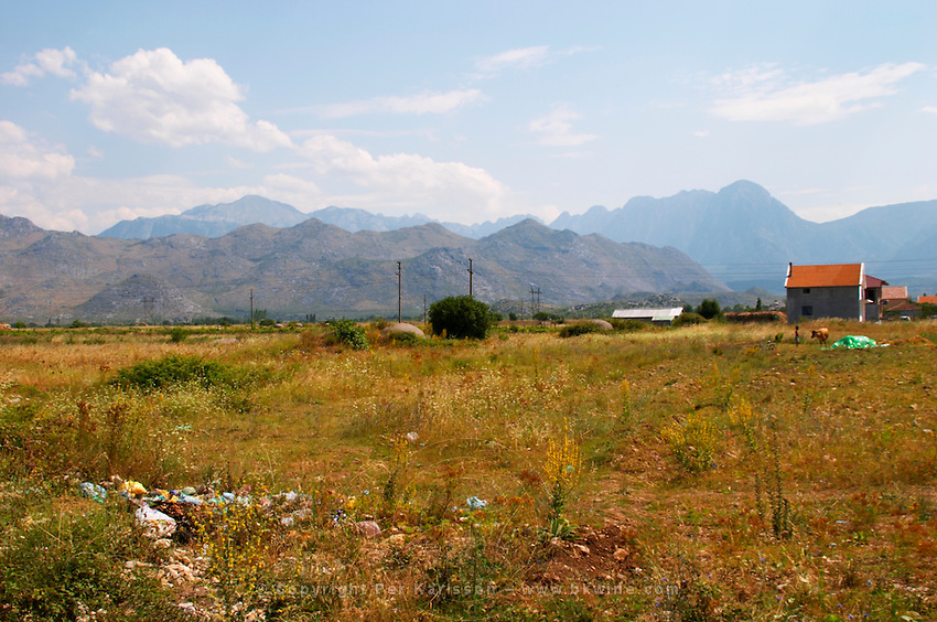 A view over the dry and desolate plain with rubbish and the Ranxe mountains in the background. On the road between Shkodra and the border to Montenegro. Albania, Balkan, Europe.