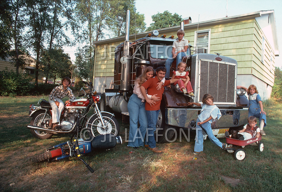 Missouri, St Joseph, 1978. Mr. Wayne and Mrs. Mary Ann Simpson and their truck in front of their house with their six kids.