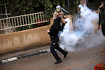 A Palestinian protester throws back a tear gas canister during clashes with Israeli security forces next to the Jewish settlement of Psagot, near the West Bank city of Ramallah, November 3, 2015. The current wave of violence erupted in mid-September, fueled by rumors that Israel was trying to increase Jewish presence in Jerusalem then quickly spread across Israel, the West Bank and the Gaza Strip. Photo by Shadi Hatem