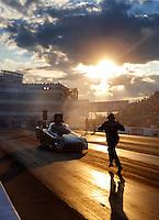 Sep 16, 2016; Concord, NC, USA; A crew member backs up NHRA funny car driver Alexis DeJoria during qualifying for the Carolina Nationals at zMax Dragway. Mandatory Credit: Mark J. Rebilas-USA TODAY Sports