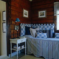 Blue and white striped fabrics have been used for the cover, cushions and headboard of this daybed