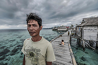 Anton (39) stands on a wooden walkway in front of his house in the Bajau stilt village of Pulo Papan. He still makes his living from the ocean, but he did not inherit the traditional free-diving skills of his father's generation.
