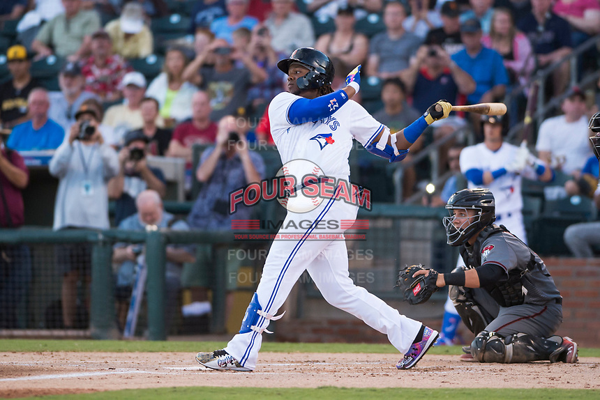 AFL West third baseman Vladimir Guerrero Jr. (27), of the Surprise Saguaros and Toronto Blue Jays organization, follows through on his swing in front of catcher Daulton Varsho (8) during the Fall Stars game at Surprise Stadium on November 3, 2018 in Surprise, Arizona. The AFL West defeated the AFL East 7-6 . (Zachary Lucy/Four Seam Images)
