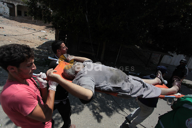 Medics evacuate an injured man from Gaza's eastern Shejaiya district on July 20, 2014. At least 40 people were killed and nearly 400 wounded in Israeli shelling of Gaza's northeastern Shejaiya district overnight, medics said. Photo by Ashraf Amra