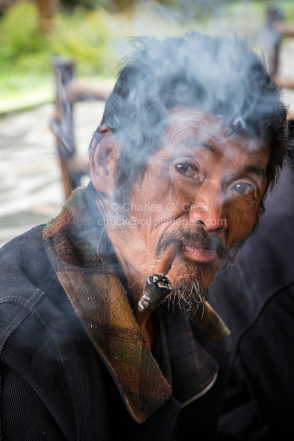 Huanggang, Guizhou, China.  Middle-aged Man of the Dong Ethnic Group Smoking his Pipe.