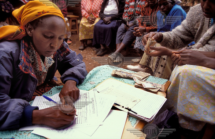 © Giacomo Pirozzi / Panos Pictures..KENYA..Woman signing for a loan as part of a micro-credit scheme run by a self-help group.