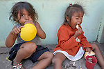Valeria Figuera (left), 2, and Fabiani Cedenho, 3, both refugees from Venezuela, sit on the ground in Boa Vista, Brazil, enjoying breakfast provided by Consolata Missionary Sisters. The girls are cousins.
