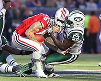Foxboro, MA  -  New England Patriots Aaron Hernandez has his helmet ripped off by NY Jets David Harris on Sunday, October 9, 2011.