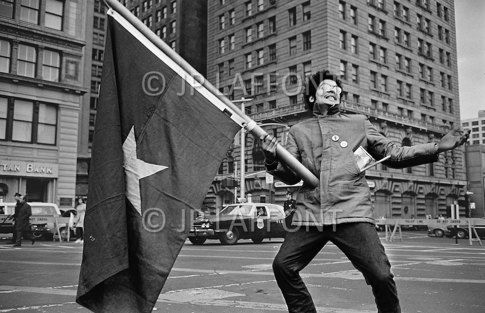 December 1969, Manhattan, New York City, New York State, USA --- An African American man holding a Vietnam flag in a demonstration in memory of Black Panther Fred Hampton killed in Chicago. Fred Hampton was a Chicago based member of the Black Panthers killed in a 1969 raid on the Illinois Black Panther headquarters because he was suspected of plotting to assassinate Federal agents and city leaders. --- Image by © JP Laffont