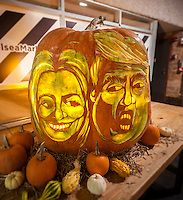 Just in time for Halloween and the Presidential election a giant pumpkin is decorated with carvings of the faces of Hillary Clinton, left,  and Donald Trump on display at Chelsea Market in New York on Friday, October 28, 2016. The images were carved by master Pumpkin Carver Hugh McMahon and the pumpkins are a tradition at Chelsea Market.  (© Richard B. Levine)