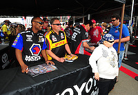 Mar. 10, 2012; Gainesville, FL, USA; NHRA funny car driver Jeff Arend and top fuel dragster driver Antron Brown sign autographs and greet fans  during qualifying for the Gatornationals at Auto Plus Raceway at Gainesville. Mandatory Credit: Mark J. Rebilas-